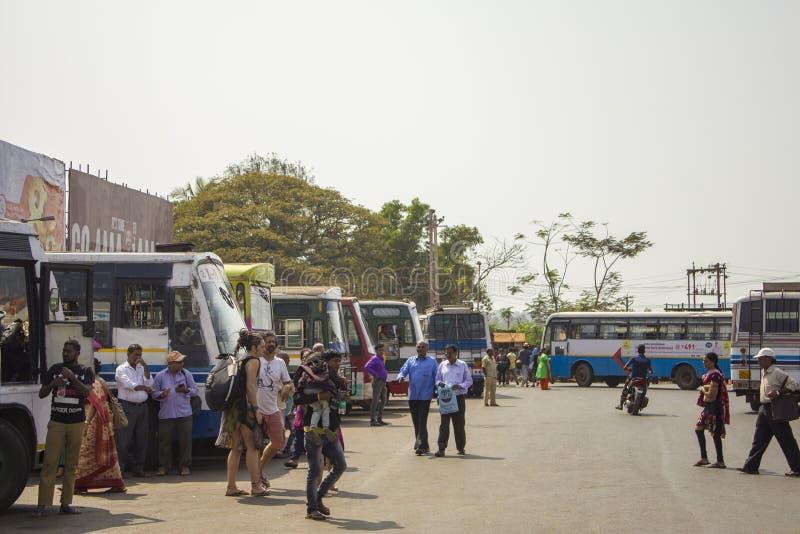 Il popolo indiano ed i turisti europei camminano nell'autostazione sui precedenti di variopinto parcheggiato fotografia stock