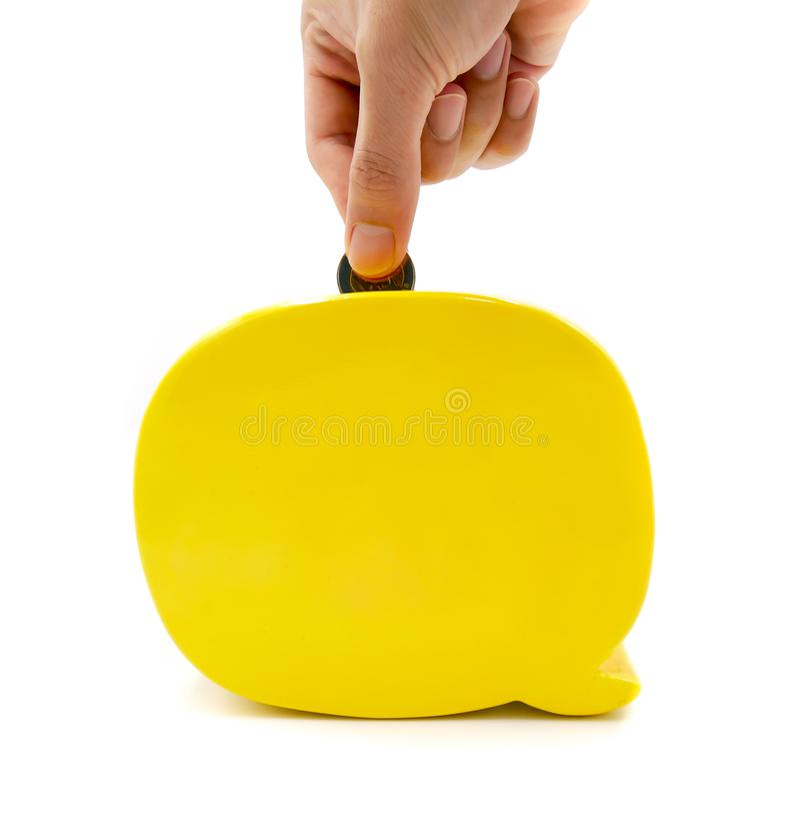 Il porcellino salvadanaio giallo moderno, mano umana sta cadendo la moneta per risparmiare i soldi rappresenta a contare, libertà fotografia stock