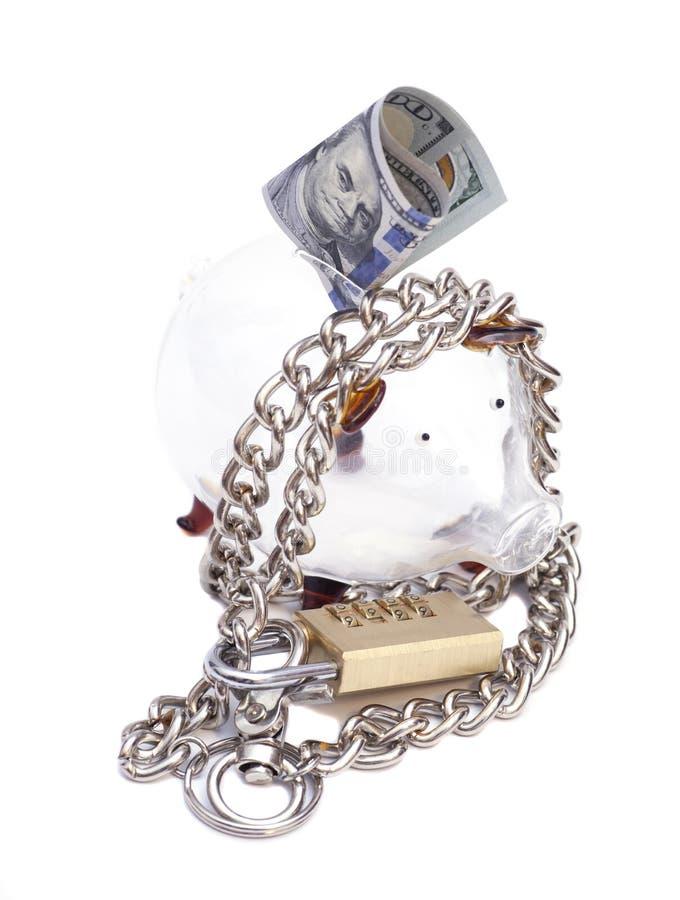 Il porcellino salvadanaio padlocked con le catene ed il lucchetto con il banknot del dollaro immagine stock