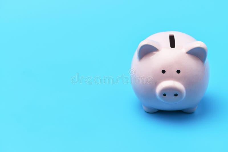 Il porcellino salvadanaio rosa sotto forma di un maiale è sui giusti precedenti blu A sinistra c'? un posto nell'ambito dell'iscr fotografie stock libere da diritti