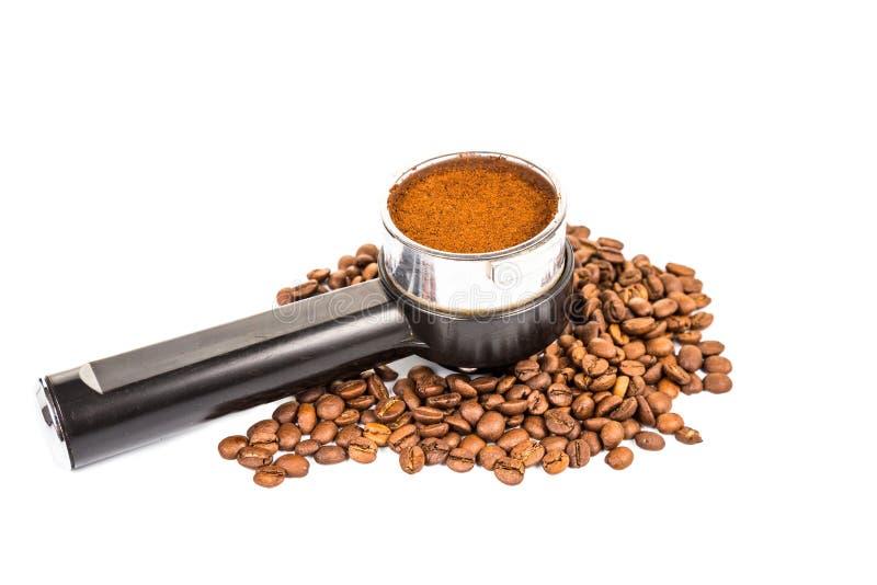 Il portafilter del caffè ha riempito di caffè con precisione a terra e con i chicchi di caffè ha sparso intorno immagini stock