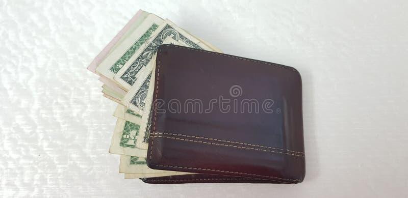 Il portafoglio in pieno di varie banconote americane del dollaro ha isolato immagini stock