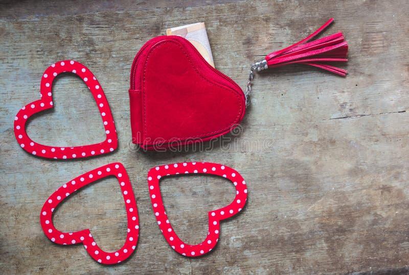 Il portafoglio rosso ed il cuore punteggiato rosso e bianco hanno modellato le decorazioni su fondo di legno fotografie stock