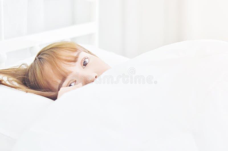 Il porte une robe blanche pour dormir photo stock