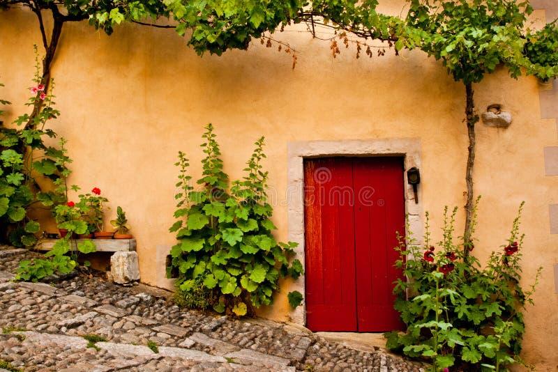 Il portello di legno rosso ha fiancheggiato dalle piante verdi fotografie stock