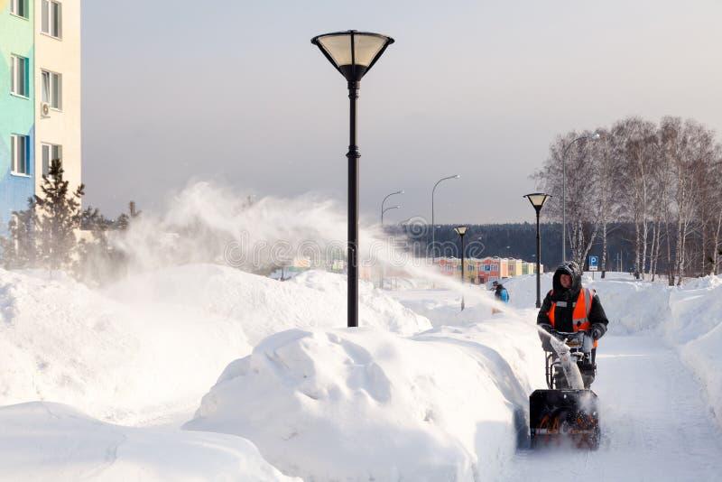 Il portiere della Russia Kemerovo 2019-02-22 in maglia arancio uniforme pulisce la pavimentazione, viale pedonale da neve con la  fotografie stock