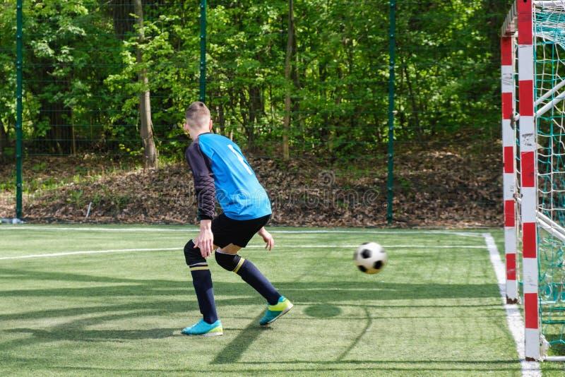 Il portiere prende la palla Gli sport del portiere dello stadio giocano il gioco di messa a terra, l'uomo del custode di calcio d fotografia stock