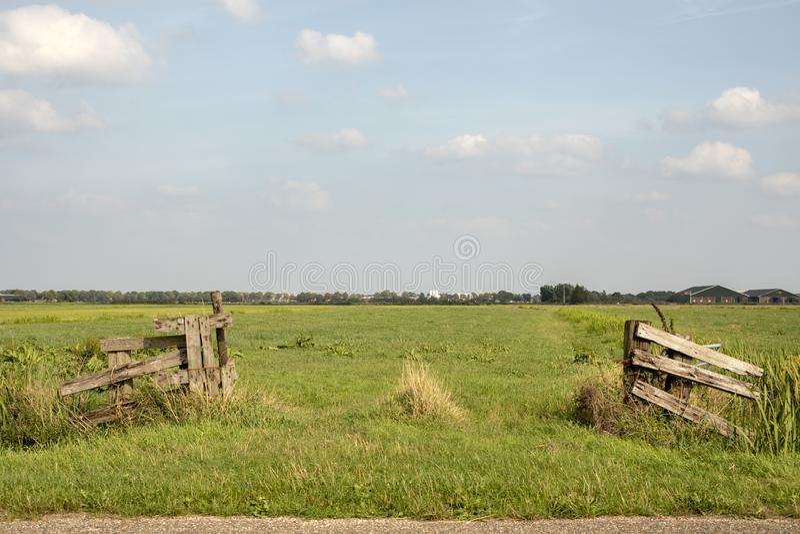 Il portone aperto di legno dilapidato è invaso con le erbacce, il pascolo e un cielo blu-chiaro con le nuvole immagine stock libera da diritti