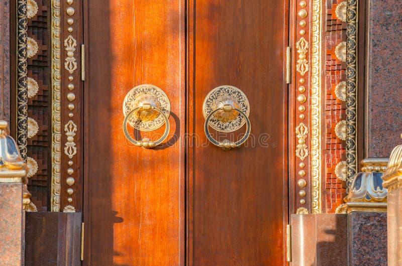 Il portone di legno antico con il battitore di porta dorato due suona la vista frontale del primo piano Vecchio frammento della p immagini stock libere da diritti