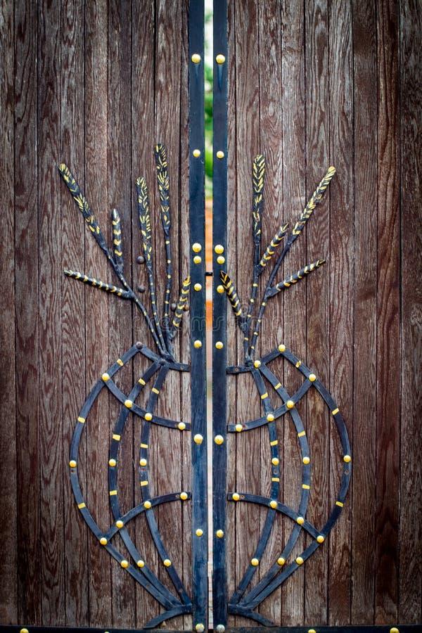 Il portone di legno con gli elementi del ferro battuto si chiude su immagini stock