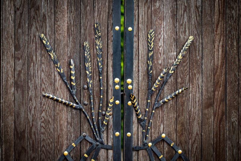 Il portone di legno con gli elementi del ferro battuto si chiude su fotografie stock libere da diritti