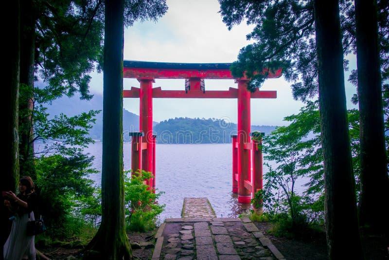 Il portone rosso luminoso di Torii ha sommerso nelle acque del lago Ashi, caldera con le montagne sui precedenti Santuario di Hak fotografia stock libera da diritti