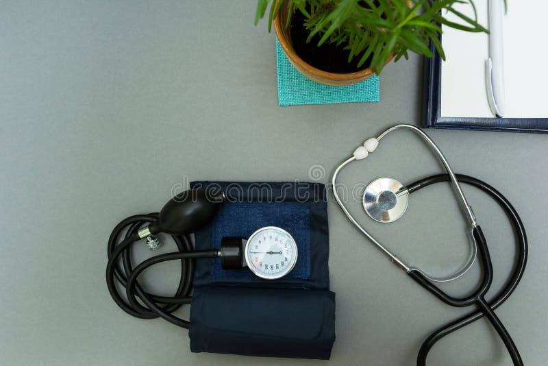 Il posto di lavoro del medico Blocco note con la penna, il tonometer, lo stetoscopio ed il vaso da fiori su un fondo grigio immagine stock libera da diritti