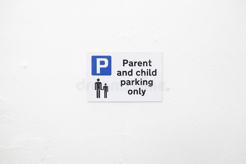 Il posto-macchina del bambino e del genitore firma soltanto dentro il parcheggio sulla parete bianca in bianco immagine stock libera da diritti