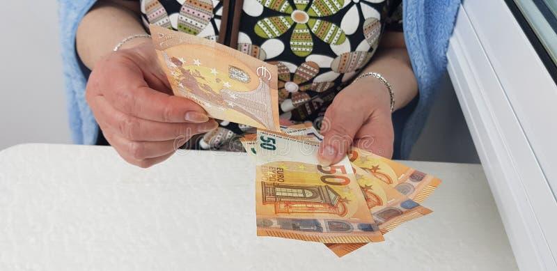 il povero senior della donna ha vestito l'euro denaro contante di conteggi immagini stock