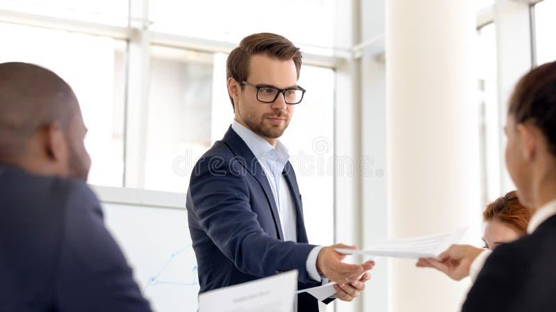 Il presentatore maschile condivide materiale distribuito ai dipendenti durante la riunione immagini stock