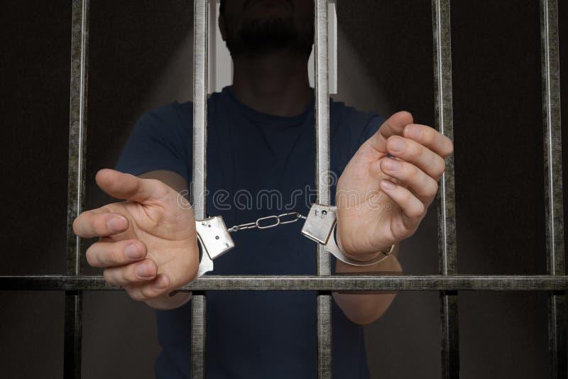 Il prigioniero arrestato sta tenendo le barre in cella di prigione immagine stock libera da diritti