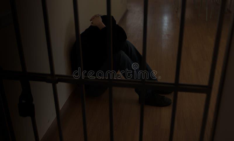 Il prigioniero dietro le barre Tenuta con le mani sulle griglie nella disperazione fotografia stock