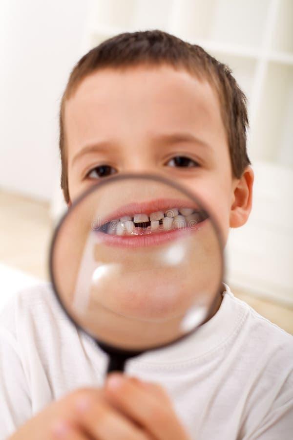 Il primo ha perso il dente - ragazzo con il magnifier fotografie stock