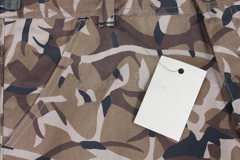 Il primo piano che la tasca marrone di camo mette/che ansima con l'etichetta immagini stock