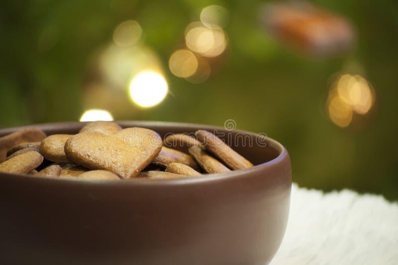 Il primo piano con i cuori dei biscotti del pan di zenzero su fondo dell'albero di Natale si accende fotografie stock libere da diritti