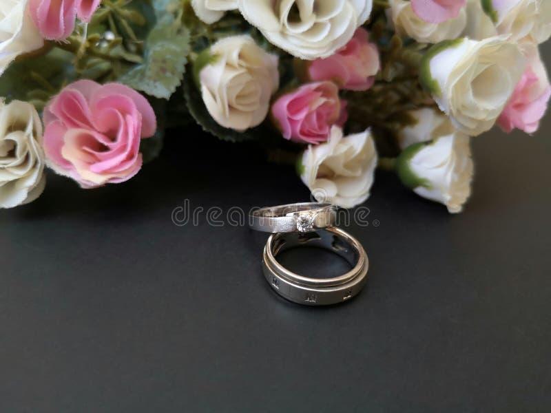 Il primo piano con le fedi nuziali e le belle rose fioriscono il fondo fotografie stock libere da diritti