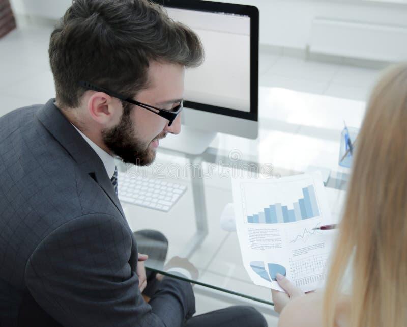 Il primo piano degli impiegati del ` s della società funziona con informazioni finanziarie immagine stock libera da diritti