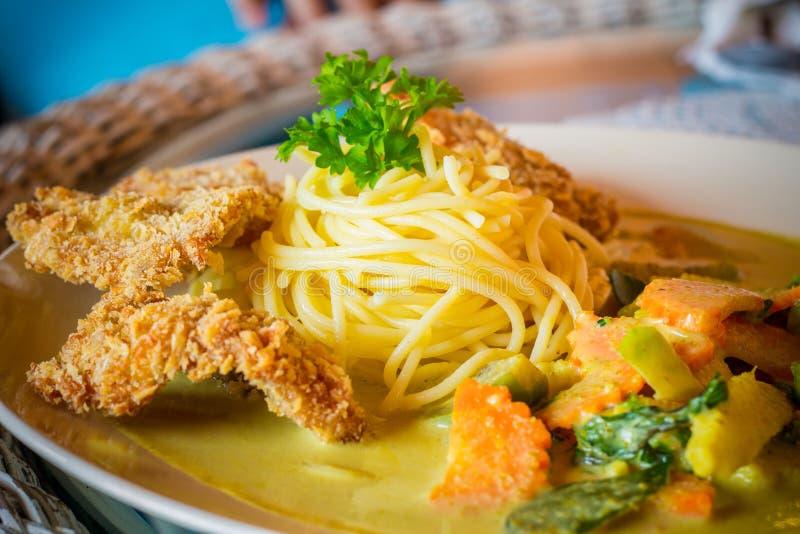 Il primo piano degli spaghetti si inverdisce il curry con carne di maiale fritta sulla tavola fotografia stock libera da diritti