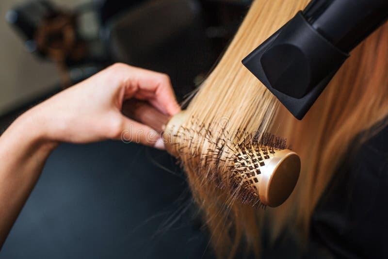 Il primo piano dei parrucchieri passa i capelli biondi di essiccazione con il fon e la spazzola rotonda Fare acconciatura nel sal fotografia stock