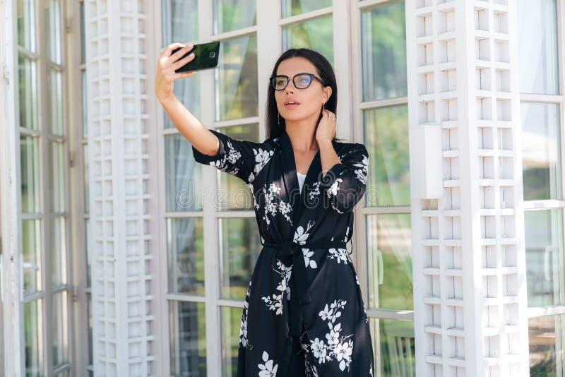 Il primo piano dei vetri d'uso di una bella ragazza ha un aspetto europeo, capelli diritti scuri, indossanti un'attrezzatura di s fotografie stock libere da diritti