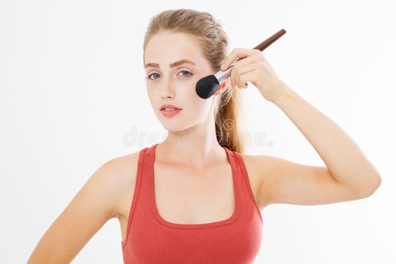 Il primo piano del fronte felice della giovane donna con compone la spazzola isolata su fondo bianco Concetto di cura di pelle de fotografia stock