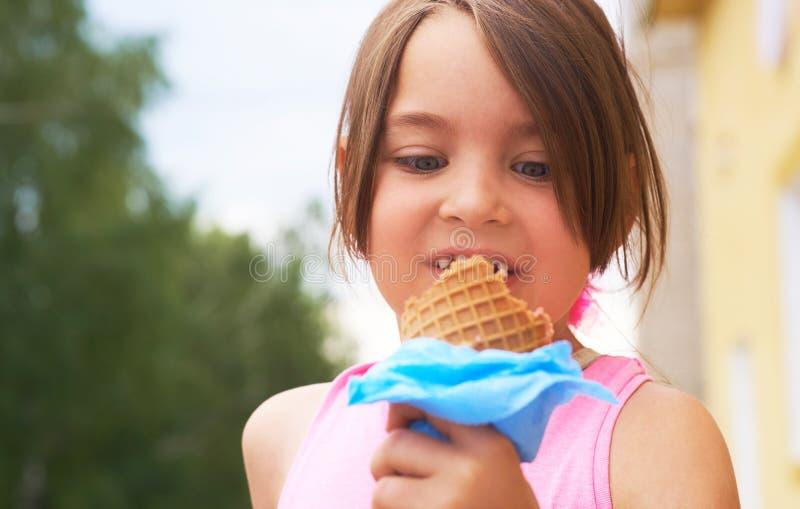 Il primo piano del gelato ha tenuto a disposizione dalla ragazza sveglia Piccola ragazza caucasica che mangia il gelato in un con fotografia stock