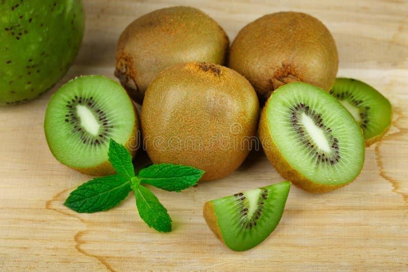 Il primo piano del kiwi verde fresco che si trova su una tavola di legno leggera, fetta di kiwi, ha accatastato il kiwi su una ta immagini stock