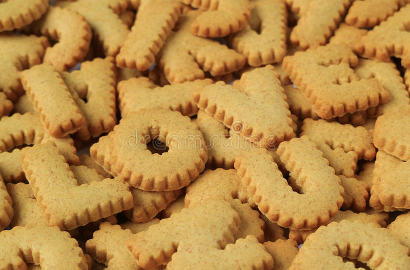 Il primo piano dell'AMORE U di parola I compitato con l'alfabeto ha modellato i biscotti sul mucchio degli stessi biscotti fotografie stock