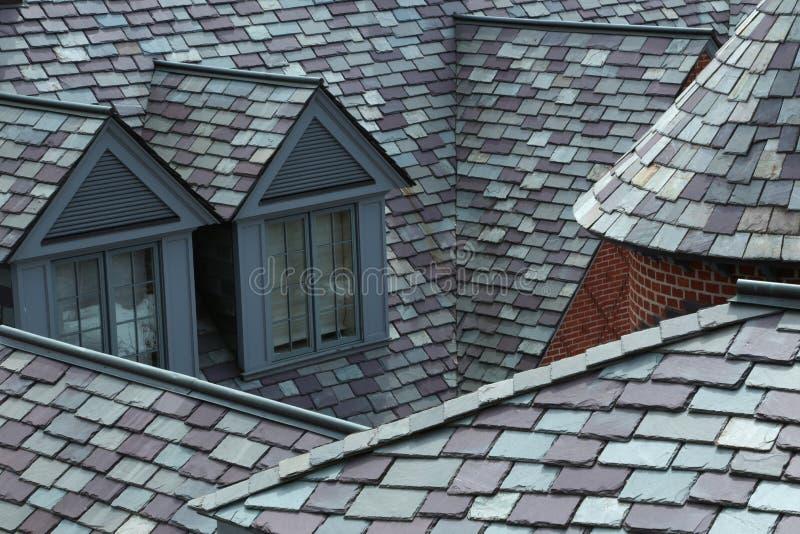 Il primo piano dell'ardesia ha piastrellato i tetti in tonalità di grey e di verde immagini stock