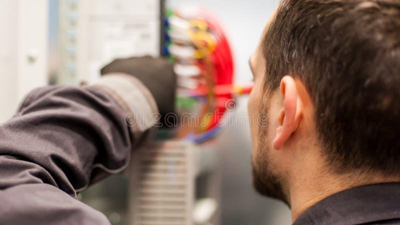 Il primo piano dell'ingegnere dell'elettricista funziona con i cavi del cavo elettrico immagine stock libera da diritti
