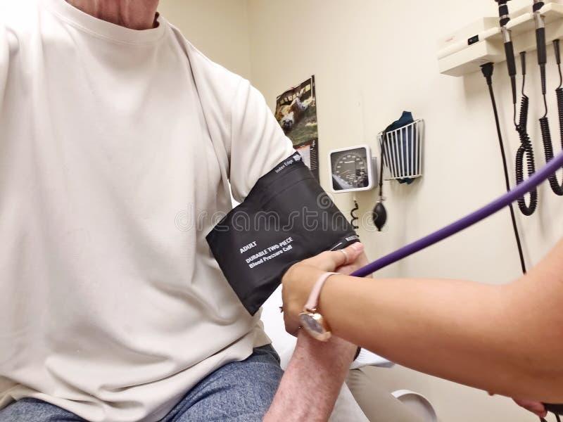 Il primo piano dell'uomo che è amministra la prova di pressione sanguigna fotografie stock