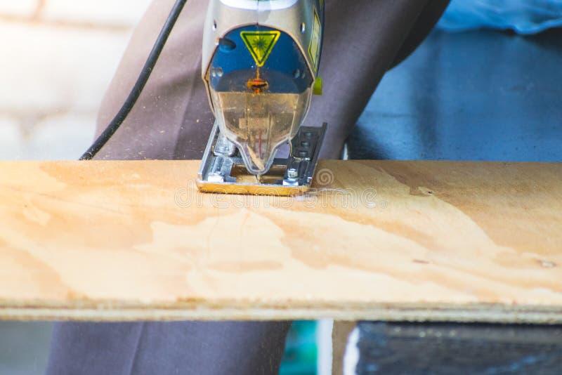 Il primo piano dell'uomo del carpentiere che usando la circolare ha visto per il taglio del legno fotografia stock