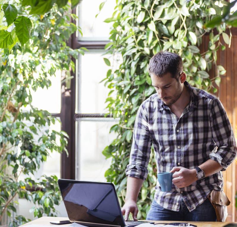 Il primo piano dell'uomo di affari gode di di lavorare al computer nel suo pleasan fotografia stock