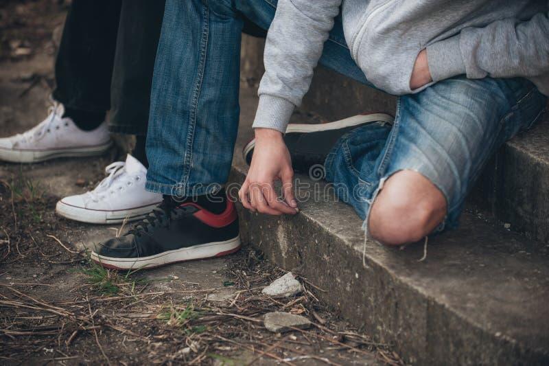 Il primo piano dell'uomo estingue un cigarett unito dell'hashish o della cannabis fotografia stock libera da diritti