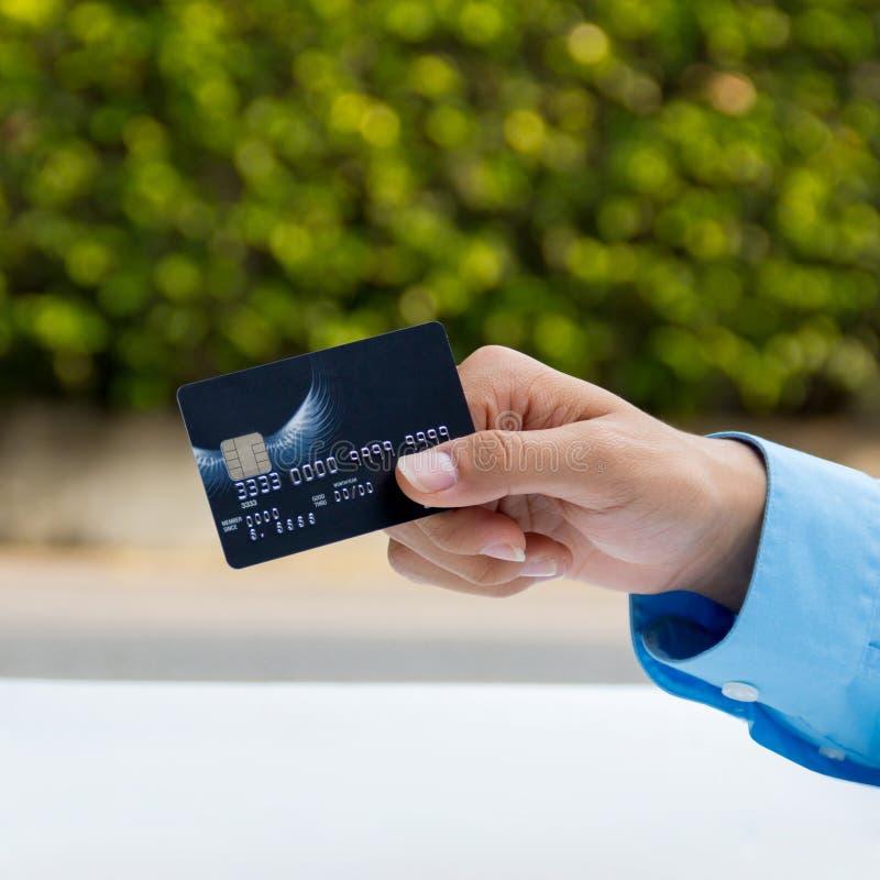 Il primo piano della carta di credito della tenuta della mano, aspetta per il pagamento fotografie stock