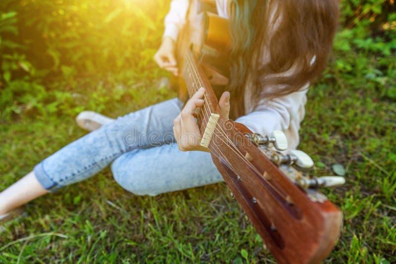 Il primo piano della donna passa il gioco della chitarra acustica sul fondo del giardino o del parco Ragazza teenager che impara  fotografia stock