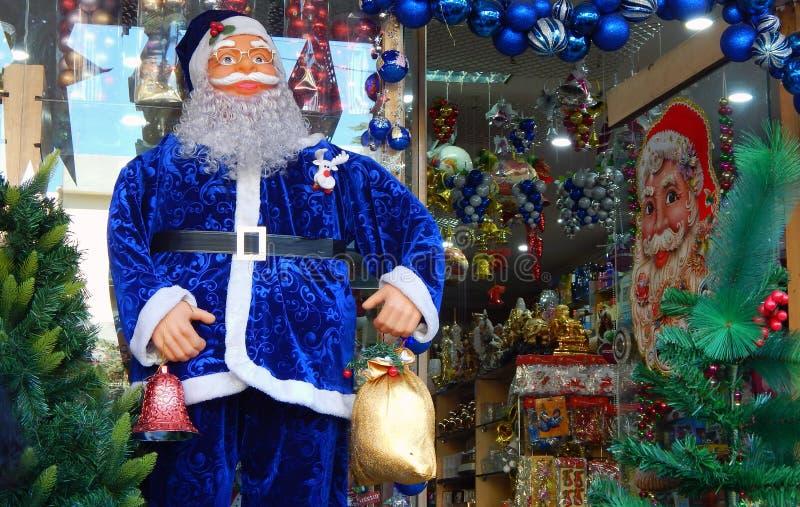 Il primo piano della figura di Santa Claus ha tenuto davanti al dettagliante che vende gli oggetti di Natale fotografia stock