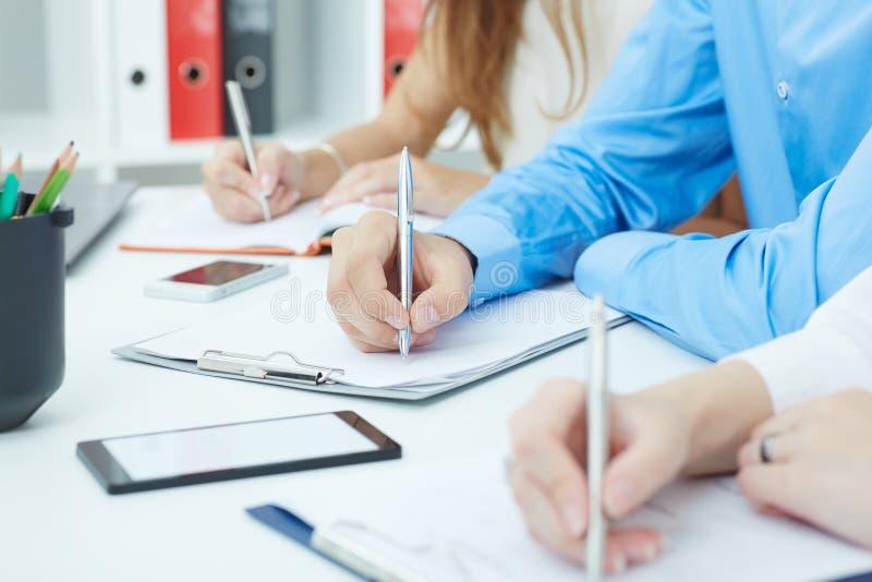 Il primo piano della gente di affari passa la fabbricazione delle note sulla riunione d'affari all'ufficio immagini stock