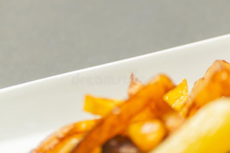 Il primo piano delle fritture dorate ha preparato dalle patate fresche, grasse ma fotografie stock libere da diritti
