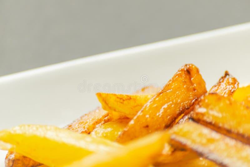 Il primo piano delle fritture dorate ha preparato dalle patate fresche, grasse ma fotografie stock