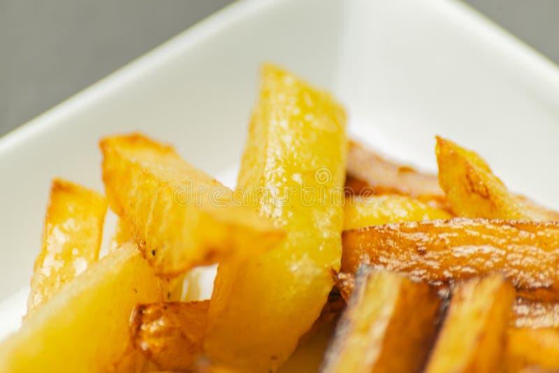 Il primo piano delle fritture dorate ha preparato dalle patate fresche, grasse ma fotografia stock