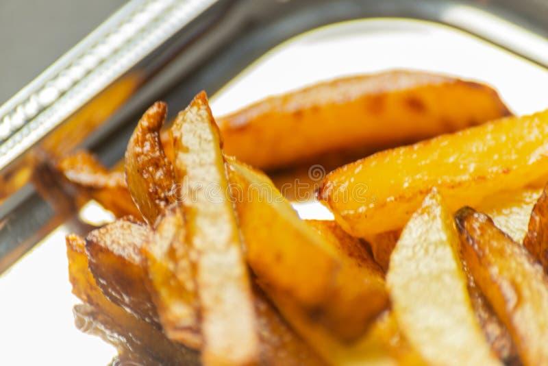 Il primo piano delle fritture dorate ha preparato dalle patate fresche, grasse ma immagini stock