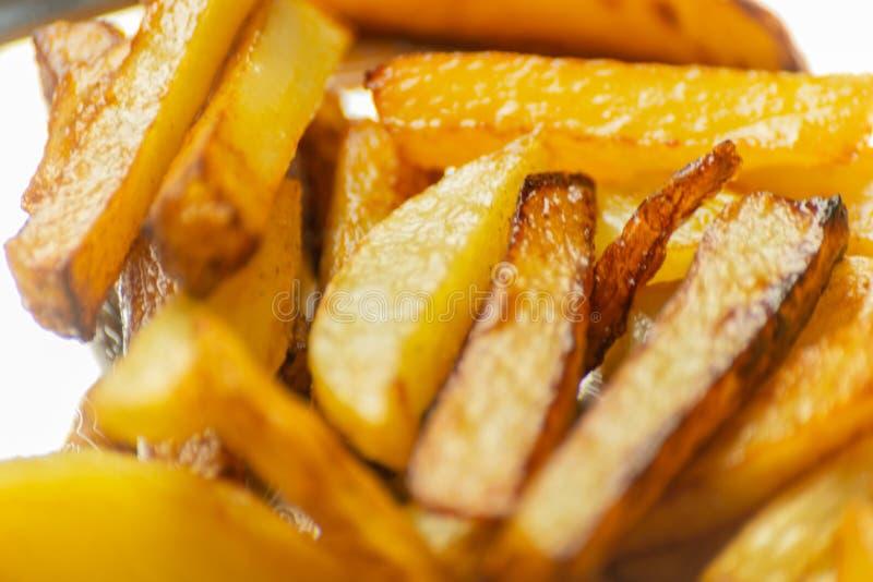 Il primo piano delle fritture dorate ha preparato dalle patate fresche, grasse ma immagine stock libera da diritti