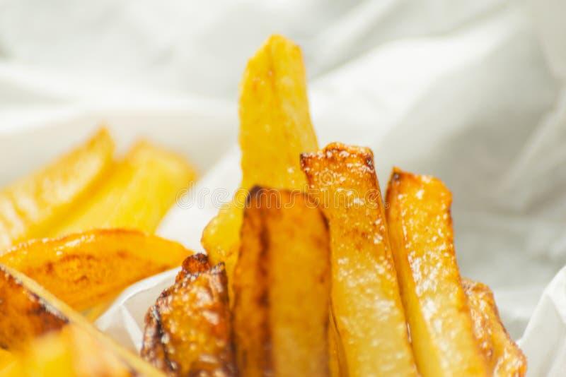 Il primo piano delle fritture dorate ha preparato dalle patate fresche, grasse ma immagine stock